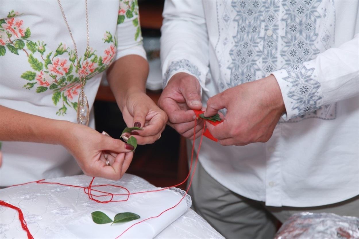 Після батьків молодят почесну місію шити весільний вінок передають вінчальним батькам.