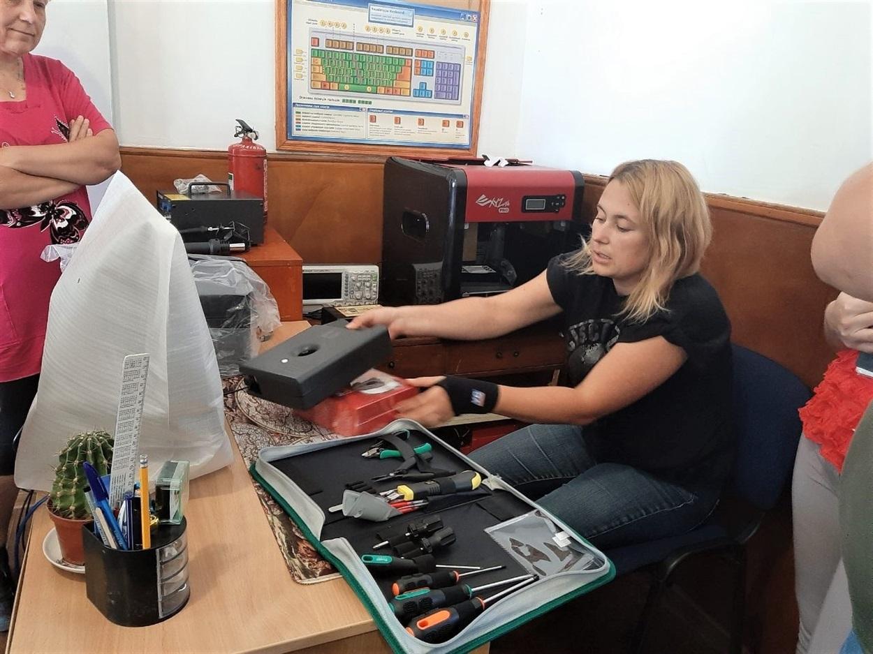 Вчителька демонструє інструменти для роботехніки та матеріали для роботи нового принтера